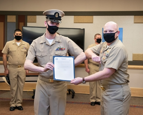 Capt. Jip Mosman, commander, Puget Sound Naval Shipyard & Intermediate Maintenance Facility, presents newly-pinned Chief Petty Officer Devin Donohue with his promotion orders during a during a ceremony Jan. 29, 2021, at Olympic Lodge on Naval Base Kitsap-Bremerton, Washington. The ceremony had limited attendees, with participants and attendees socially distanced to adhere to COVID-19 protective protocols.