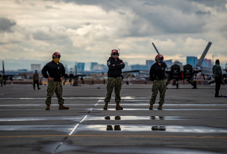 U.S. Navy Airmen stand on the flight line.