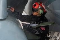 U.S. Navy Airman works on aircraft.