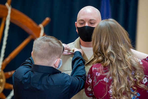 Chief Intelligence Specialist Joshua Waldrop of U.S. Fleet Forces Command (USFFC) receives his anchors from his family during a chief petty officer (CPO) pinning ceremony at the USFFC headquarters in Norfolk, Virginia.