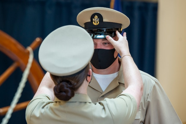 Chief Intelligence Specialist Joshua Waldrop of U.S. Fleet Forces Command (USFFC) receives his cover during a chief petty officer (CPO) pinning ceremony at the USFFC headquarters in Norfolk, Virginia.