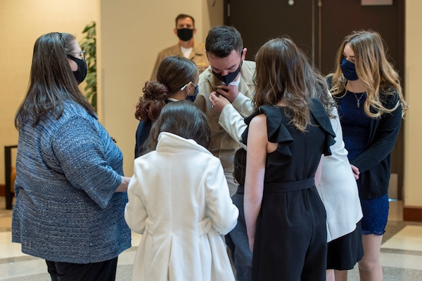 Chief Aviation Aerographer's Mate Travis Strait of U.S. Fleet Forces Command (USFFC) receives his anchors from his family during a chief petty officer (CPO) pinning ceremony at the USFFC headquarters in Norfolk, Virginia.