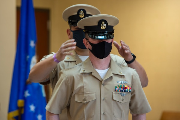Chief Aviation Aerographer's Mate Travis Strait of U.S. Fleet Forces Command (USFFC) receives his cover during a chief petty officer (CPO) pinning ceremony at the USFFC headquarters in Norfolk, Virginia.