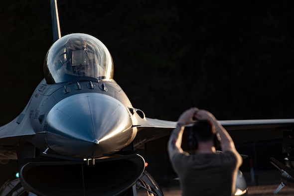 Image of an Airman using hand signals in front of an F-16 Viper.