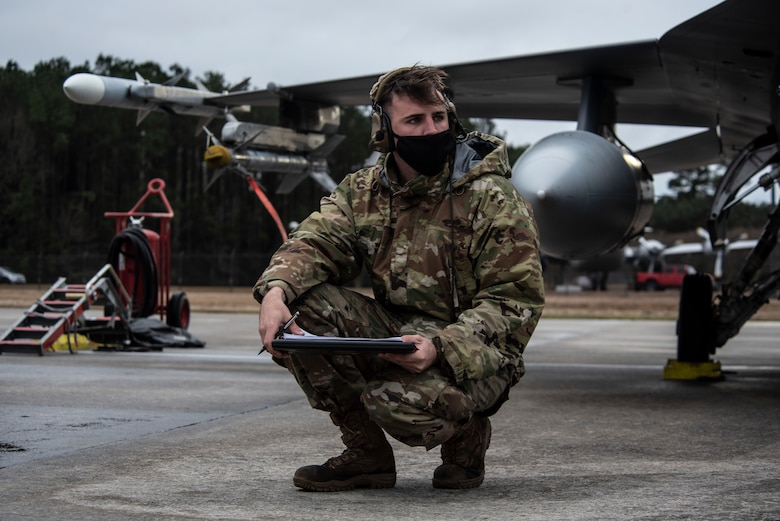 Image of an Airman writes things down in a notebook in front of an F-16.
