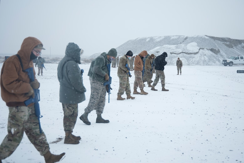 A group of Airmen walks and search for simulated unexploded ordnance.