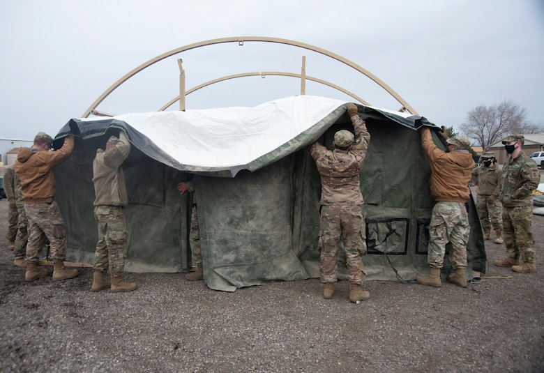 A group of Airmen lifts a door frame of a small shelter system tent.