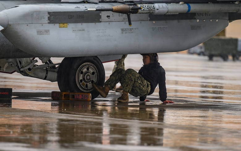 U.S. Navy airman works on aircraft.