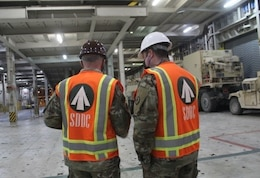 Capt. Christopher Lang, 1185th Deployment and Distribution Support Battalion, and Maj. Gregory Gemedschiew, 1185th DDSB, discuss the loading plan for 2nd Armored Brigade Combat Team, 1st Armored Division, equipment aboard the Green Ridge at the Port of Shuaiba, Kuwait, Jan. 22, 2021. The equipment, bound for the United Arab Emirates, will be received by 2/1 ABCT Soldiers and is scheduled to be utilized during exercise Iron Union 14. (U.S. Army photo by Claudia LaMantia)