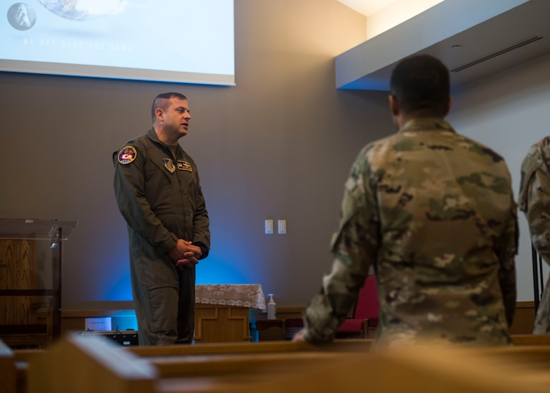 Military members talking to each in a chapel .