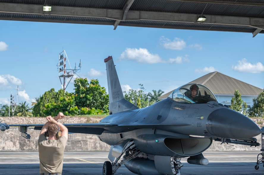 A man crosses his arms above his head in front of a fighter jet.