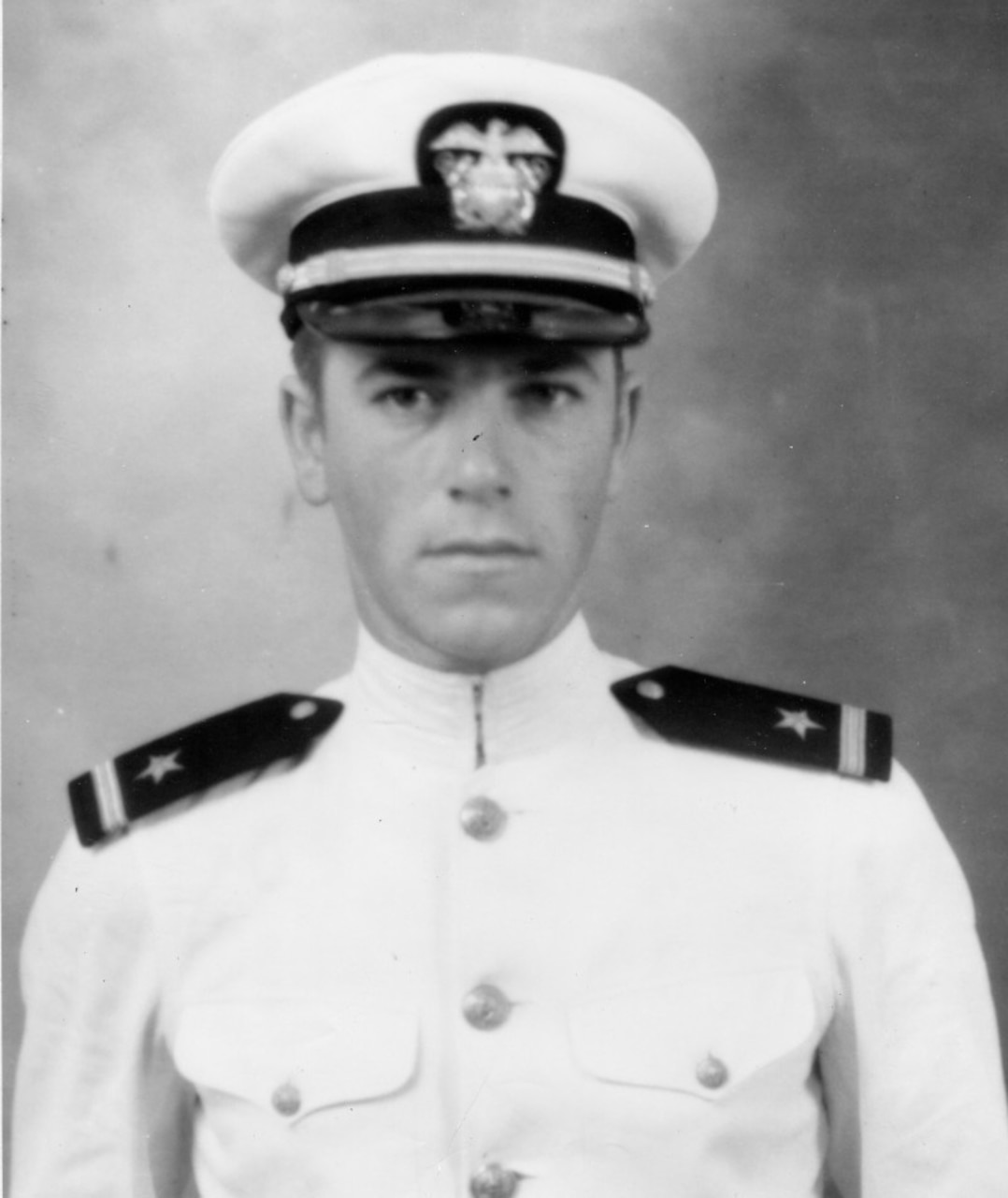A young sailor in his white dress uniform and cap looks forward.