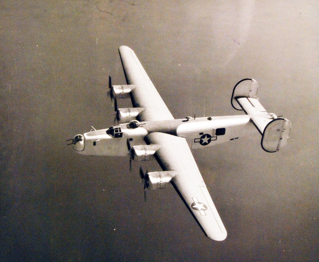 A four-propeller airplane flies in the air.