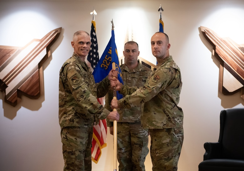 U.S. Air Force Col. Steven Collen (left), 325th Maintenance Group commander, gives command of the 325th Munitions Squadron to Maj. Justin Cassidy (right), during an activation ceremony at Tyndall Air Force Base, Florida, June 29, 2021. The 325th MUNS is tasked with safeguarding and maintaining Tyndall's $275 million in munitions in support of projecting unrivaled combat airpower. (U.S. Air Force photo by Staff Sgt. Stefan Alvarez)