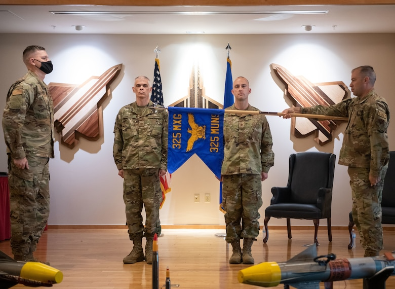The official guidon of the 325th Munitions Squadron is unveiled at an activation ceremony at Tyndall Air Force Base, Florida, June 29, 2021. The 325th MUNS supports the requirements of the United States Air Force Weapons School, Weapons Instructor Course, Air Force Civil Engineer Center, Air Force Research Lab, and the Naval Diving and Salvage Training Center. (U.S. Air Force photo by Staff Sgt. Stefan Alvarez)
