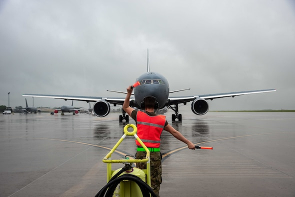 U.S. Air Force Airman 1st Class Reilly Avery, 22nd Aircraft Maintenance Squadron crew chief, marshals out a KC-46A Pegasus at McConnell Air Force Base, Kansas, June 30, 2021. The Aircraft delivered 60,000 pounds of fuel in support of Bat Wars training exercise. (U.S. Air Force photo by Airman 1st Class Zachary Willis)