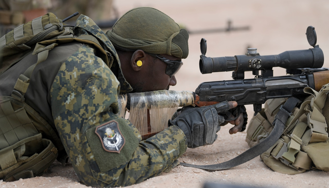 A soldier lays on the ground and aims a rifle.