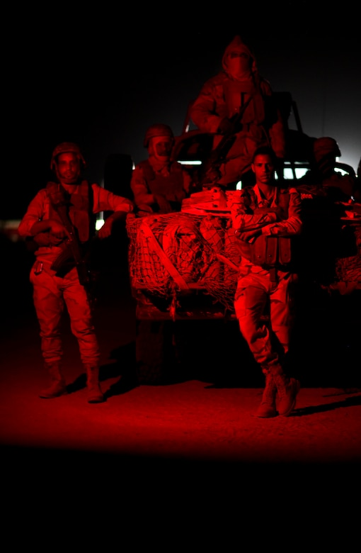 Military personnel stand at the rear of a military vehicle at night.