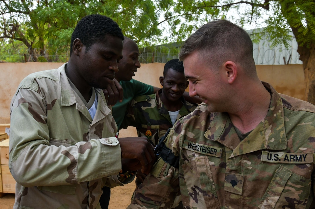 A soldier adjusts gear on the arm of another soldier.