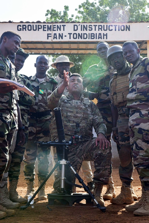 A soldier kneels in front of a weapon while soldiers stand around him.