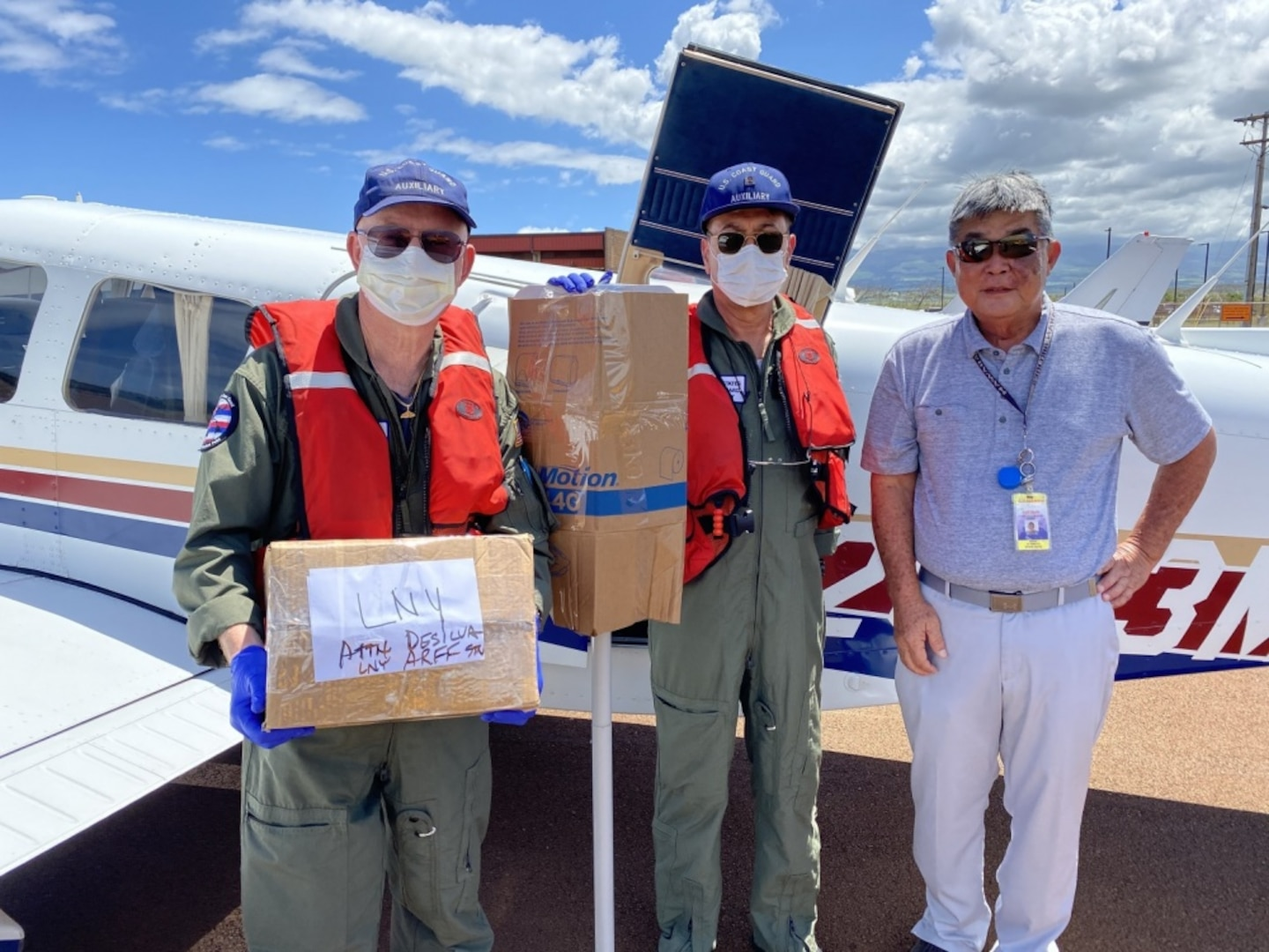 A Coast Guard Auxiliary aircrew (left) stands with Brian Kamimoto (right), assistant airport superintendent Maui District at the Maui Airport Fire Station while picking up response supplies for delivery from Maui to Lanai, March 28, 2020. The pilots transported COVID-19 supplies, including temperature reading thermometers and hand sanitation equipment, from the Maui Airport Fire Station to personnel at Lanai Airport for use by airport staff. (U.S. Coast Guard photo by Berry Redmayne/Released)