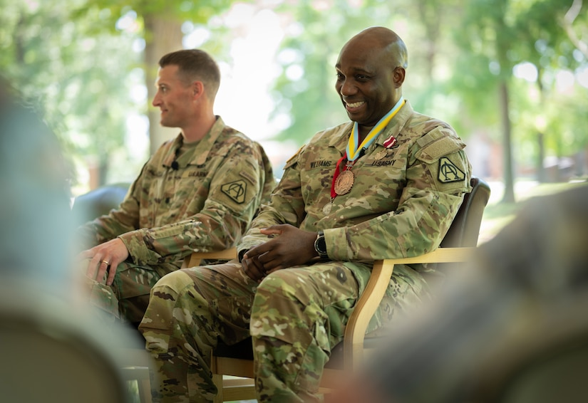 Incoming and outgoing Product Managers Soldier Precision Targeting Devices, Lt Cols. Aaron Pearsall and Jamal Williams respectively, sit together during their Change of Charter ceremony at Fort Belvoir, VA.