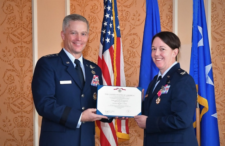 Photo of an individual receiving an award from another individual.