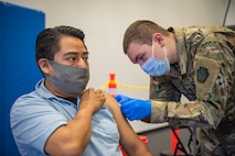 Spc. Christopher Valencia, combat medical specialist with Headquarters and Headquarters Company, 1st Battalion, 112 Infantry Regiment administers a COVID-19 vaccine to Romero Sergio at the Esperanza Community Vaccination Center in Philadelphia ON May 17, 2021. The Pennsylvania National Guard has been supporting COVID-19 vaccine sites across the Commonwealth since mid-March. PA Guard members have supported the administration of more than 500,000 COVID-19 vaccine doses. (Air National Guard photo by Staff Sgt. Ross Alexander Whitley / 111th Attack Wing)