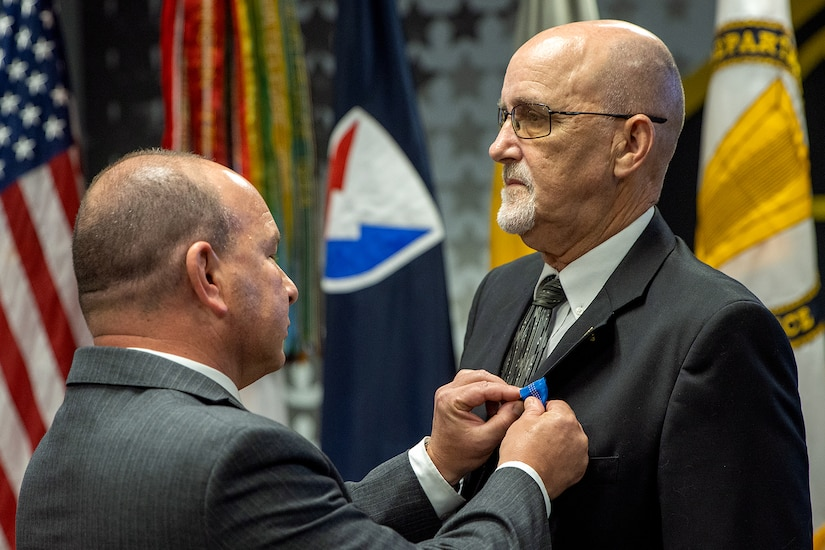 Barry W. Hoffman, U.S. Army Financial Management Command executive director, pins an Army Distinguished Civilian Service Medal on G. Eric Reid, a recently retired USAFMCOM Military Pay Operations director, during a special ceremony at the Maj. Gen. Emmett J. Bean Federal Center in Indianapolis May 26, 2021. The medal is the highest award given by the Secretary of the Army to Army civilian employees. (U.S. Army photo by Mark R. W. Orders-Woempner)