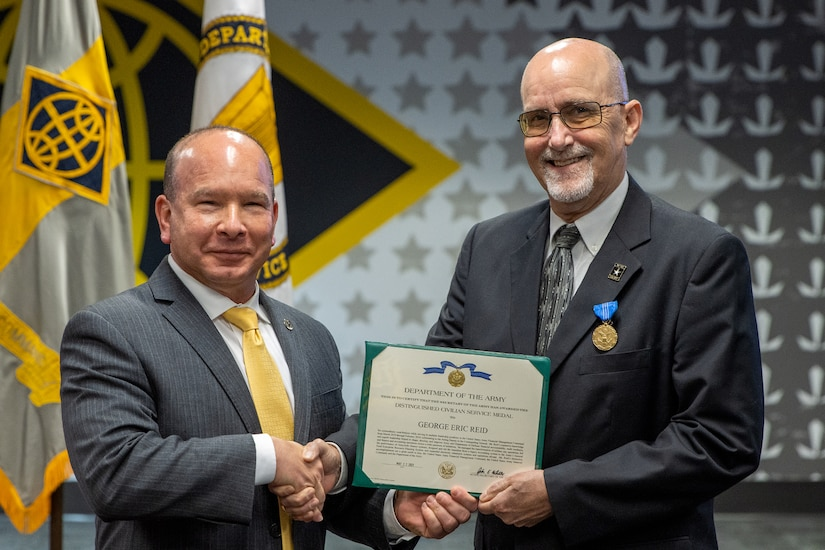 Barry W. Hoffman, U.S. Army Financial Management Command executive director, presents G. Eric Reid, a recently retired USAFMCOM Military Pay Operations director, with an Army Distinguished Civilian Service Medal during a special ceremony at the Maj. Gen. Emmett J. Bean Federal Center in Indianapolis May 26, 2021. The medal is the highest award given by the Secretary of the Army to Army civilian employees. (U.S. Army photo by Mark R. W. Orders-Woempner)