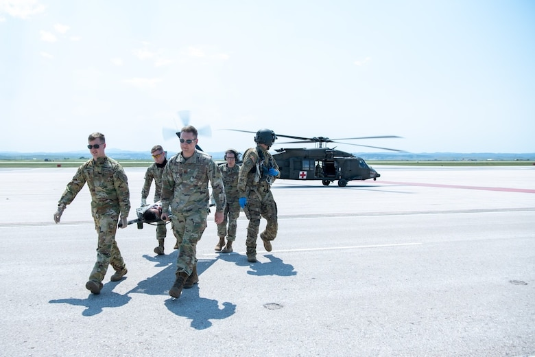 Participants in exercise Golden Coyote carry a simulated injured Army National Guardsman across the flight line on Ellsworth Air Force Base, S.D., June 16, 2021.