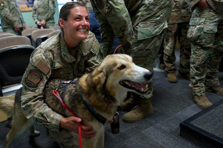 Sparky, a sled dog belonging to Iditarod musher Aliy Zirkle, visits Alaska Air National Guard Capt. Kelly Buschelman, 210th Rescue Squadron, June 28, 2021, at Joint Base Elmendorf-Richardson, Alaska. Airmen of 210th Rescue Squadron and 212th Rescue Squadron rescued Zirkle March 9 at the Iditarod Rohn checkpoint after she suffered a head injury.