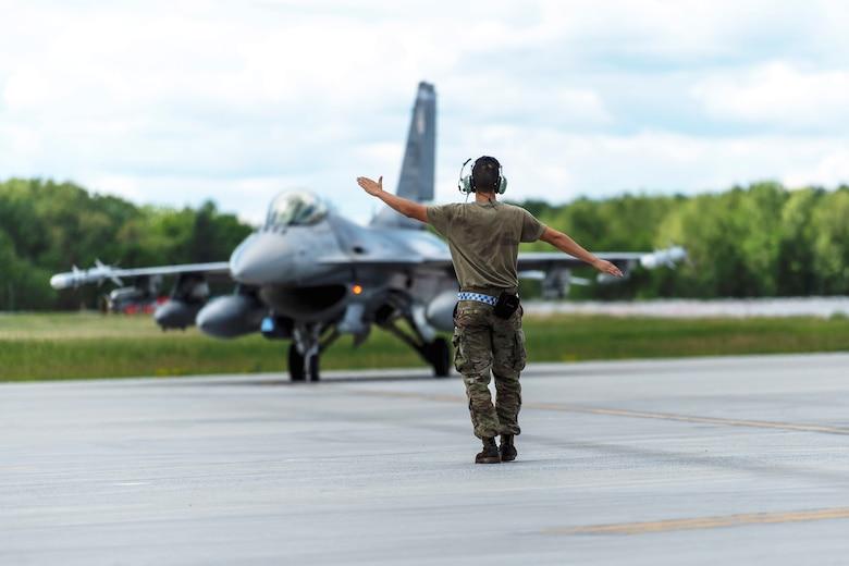 Photo of U.S. Airmen marshals aircraft.