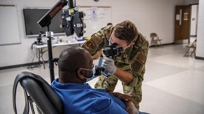 Capt. Adam Fannin, 445th Aerospace Medicine Squadron optometrist, assesses a patient at Jenkins County High School, Waynesboro, Georgia as part of East Central Georgia Medical Innovative Readiness Training, June 9, 2021.