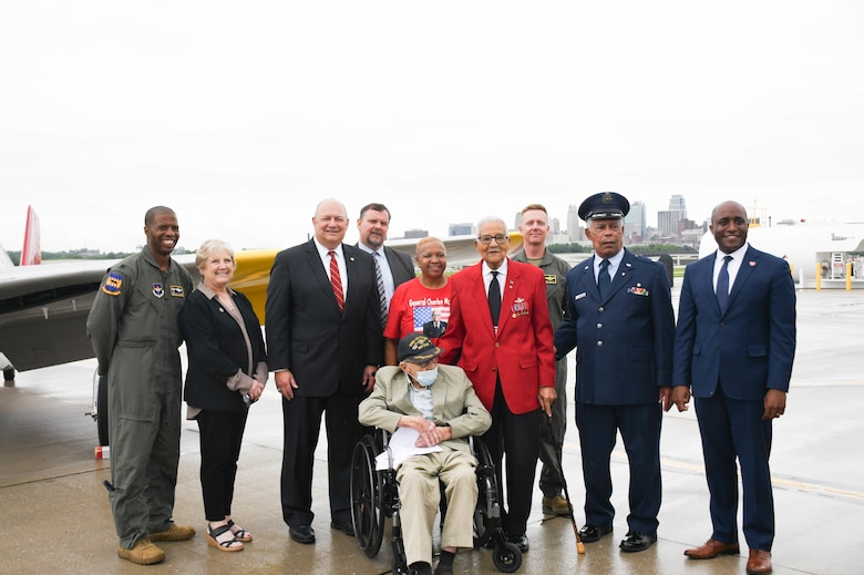 Speakers from the rededication ceremony pose for a photo near a Red-Tail P-51 Mustang painted to honor the Tuskegee Airmen