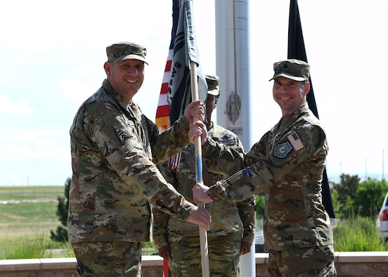 Lt. Col. Brandon Davenport, outgoing 2nd Space Warning Squadron commander, passes the guidon to Col. Richard Bourquin, Space Delta 4 commander, during a change of command ceremony at Buckley Space Force Base, Colo., July 1, 2021. The passing of the guidon is a military tradition that symbolizes a transfer of command and commemorates past leadership and success of the outgoing commander. (U.S. Space Force photo by Airman 1st Class Haley N. Blevins)