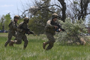Three North Dakota Air National Guard 219th Security Forces Squadron members in uniform with M4 rifles configured for training run to get into position for a training exercise at the Minot Air Force Base, N.D., June 24, 2021.