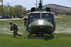 Two members of the North Dakota Air National Guard 219th Security Forces Squadron in military uniform jump out of the open door of a UH-1N Huey helicopter as the pilot and co-pilot sit in the cockpit during a training exercise at the Minot Air Force Base, N.D., June 24, 2021.