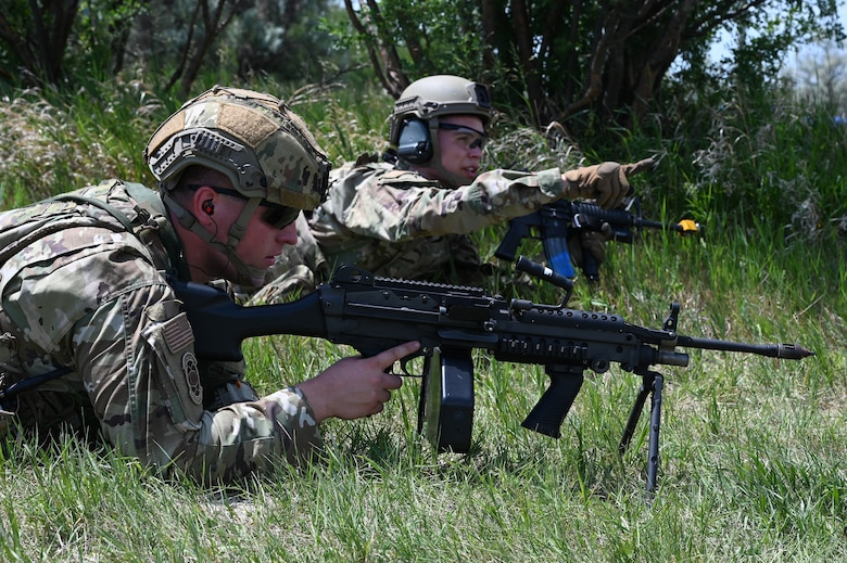 Two North Dakota Air National Guard 219th Security Forces Squadron members in military uniform with rifles modified for training lay on their stomachs during a training exercise at the Minot Air Force Base, N.D., June 24, 2021.