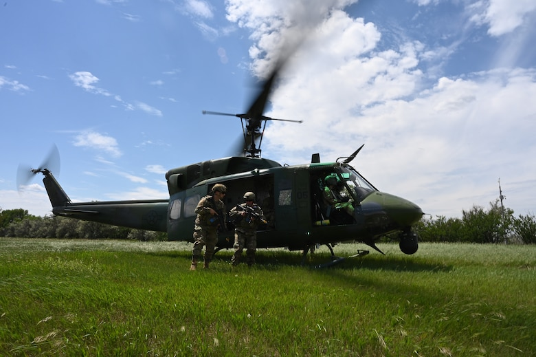 Two members of the 219th Security Forces Squadron in military uniform hop off a UH-1N Huey helicopter with rotor blades in motion during a training exercise at the Minot Air Force Base, N.D., June 24, 2021.