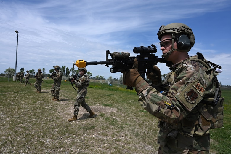 Seven members of the 219th Security Forces Squadron 219th Security Forces Squadron walk spread out in a line as they point M4 rifles ahead of them during a training exercise on a training missile launch facility at the Minot Air Force Base, N.D., June 24, 2021.