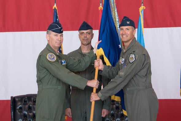 Three men holding a flag