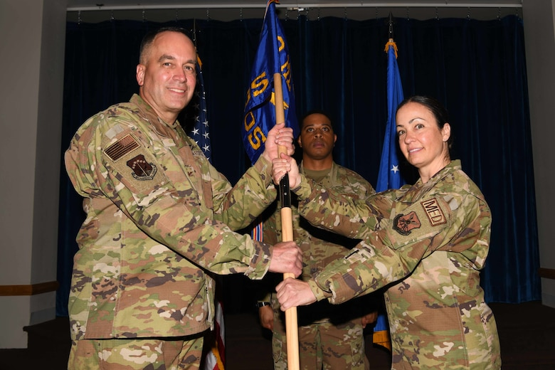 Col. Paul Toth, 90th Medical Group commander, passes the guidon to Lt. Col. Deborah Willis, 90th Healthcare Operations Squadron, during the 90 HCOS change of command ceremony July 1, 2021, at Trails End on F.E. Warren Air Force Base, Wyoming. The ceremony signified the transition of command from Col. David Barker to Willis. (U.S. Air Force photo by Airman 1st Class Charles Munoz)