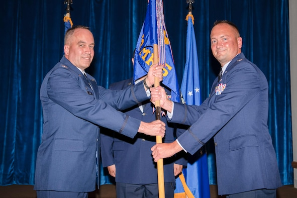 Col. Paul Toth, 90th Medical Group commander, passes the guidon to Lt. Col. Troy Novak, 90th Operational Medical Readiness Squadron, during the 90 OMRS Change of Command Ceremony July 1, 2021, at Trails End on F.E. Warren Air Force Base, Wyoming. The ceremony signified the transition of command from Col. Erin Knightner to Novak. (U.S. Air Force photo by Airman 1st Class Charles Munoz)