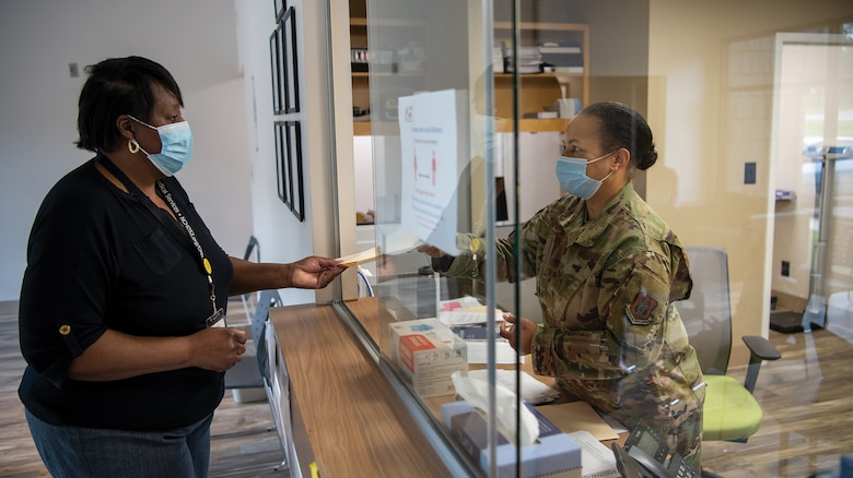 Tech. Sgt. Angela Thompson, 445th Aeromedical Staging Squadron medical administrator, hands a chart to a patient prior to receiving care at Hancock County Health Department, Hancock, Georgia, as part of the East Central Georgia Medical Innovative Readiness Training conducted on June 10, 2021.