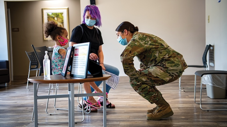 Tech. Sgt. Caitlin Donnelly, 445th Aeromedical Staging Squadron medical technician, talks to a young patient prior to receiving care at Hancock County Health Department, Hancock, Georgia, June 10, 2021.