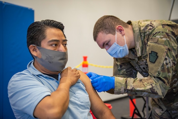 Spc. Christopher Valencia, combat medical specialist with Headquarters and Headquarters Company, 1st Battalion, 112 Infantry Regiment administers a COVID-19 vaccine to Romero Sergio at the Esperanza Community Vaccination Center in Philadelphia on May 17, 2021.
