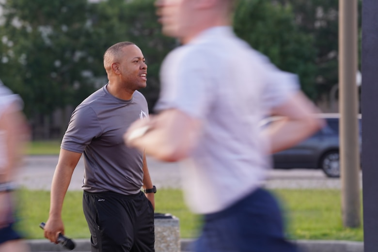 """U.S. Air Force Tech. Sgt. Alvin Morris, 336th Training Squadron master military training leader, motivates Airmen in training during physical training at the Triangle track on Keesler Air Force Base, Mississippi, June 29, 2021. """"An MTL consistently enforces standards of conduct and expectations to develop Airmen to be prepared to enter the operational Air Force,"""" said Morris. """"We are the professional example for Airmen to emulate and first look at what a healthy leadership team looks like. It is our responsibility to inspire Airmen to take pride in serving and exhibit excellence in all we do."""" (U.S. Air Force photo by Senior Airman Spencer Tobler)"""
