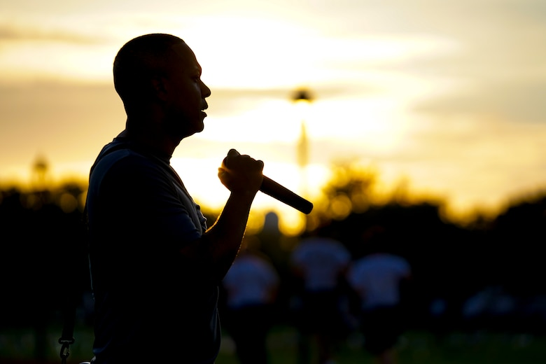 """U.S. Air Force Tech. Sgt. Alvin Morris, 336th Training Squadron master military training leader, motivates Airmen in training at the Triangle track on Keesler Air Force Base, Mississippi, June 29, 2021. """"An MTL consistently enforces standards of conduct and expectations to develop Airmen to be prepared to enter the operational Air Force,"""" said Morris. """"We are the professional example for Airmen to emulate and first look at what a healthy leadership team looks like. It is our responsibility to inspire Airmen to take pride in serving and exhibit excellence in all we do."""" (U.S. Air Force photo by Senior Airman Spencer Tobler)"""