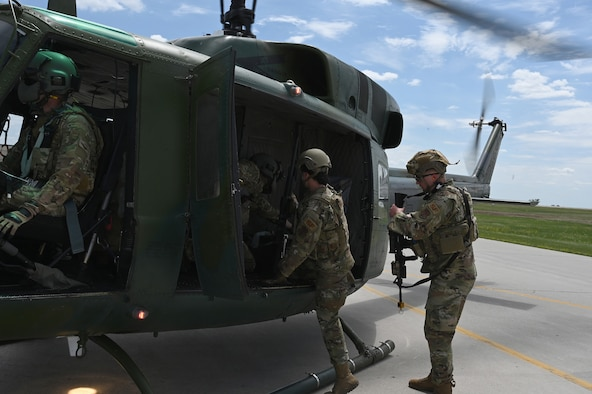 Two North Dakota Air National Guard 219th Security Forces Squadron members in uniform climb into the open door of a UH-1N Huey helicopter as it prepares for launch at the Minot Air Force Base, N.D., June 24, 2021.